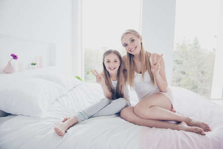 Photo pour Happiness mom mum mommy mama vacation holiday concept. Portrait photo of beautiful cute lovely excited cheerful with beaming toothy smile girls showing two fingers sitting on white linens bedclothes - image libre de droit