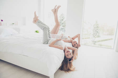 Photo pour Freedom feeling facial emotion expressing concept. Pretty beautiful cute excited childish joyful lovely nice glad attractive wearing clothes for sleeping girls holding legs up lying on bed bare foot - image libre de droit