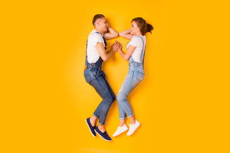 Foto de Feelings legs shoes sneakers concept. Full length high angle size photo portrait of two stylish cute lovely in denim outfit spouses enjoying life looking at each other isolated on bright background - Imagen libre de derechos