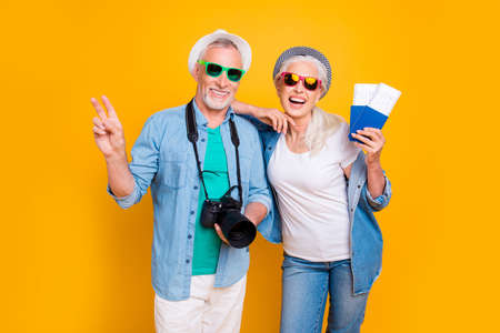 Foto de Tourism tourists traveler journey rest weekend vacation holiday relax concept. Photo portrait of excited guy two fingers digicam  lady vip passengers showing document with tickets isolated background - Imagen libre de derechos