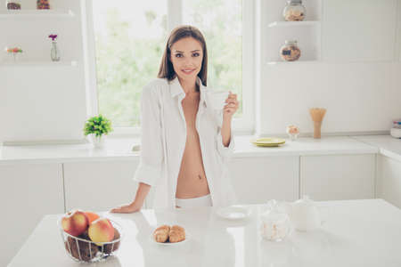 Foto de Successful and confident woman on a morning coffee break, resting and enjoying the drink. Young girl in white panties and long shirt with naked shoulder and chest stand on the kitchen of the house - Imagen libre de derechos