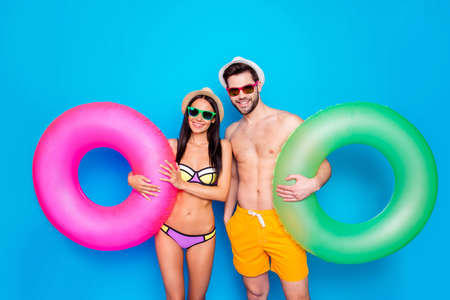 Photo for Concept of summer vacation and honeymoon. Guy and girl dressed in beachwear hold inflatable life ring standing isolated on blue background - Royalty Free Image