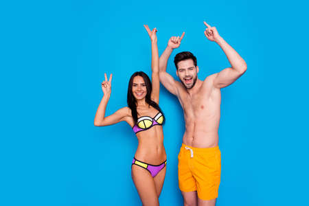 Photo pour Party mood! Handsome brunette and attractive young woman celebration vacation time with rise hands up and make v-sign isolated on blue background - image libre de droit