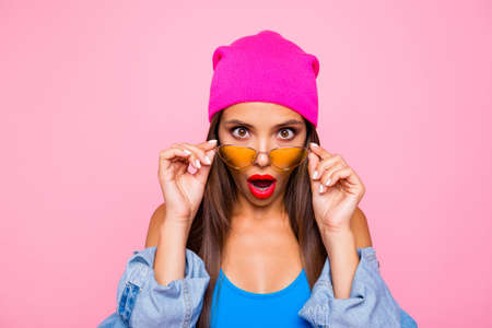 Foto de WOW! Close up portrait of shocked girl face looks over the glasses directly at the camera isolated on bright pink background - Imagen libre de derechos