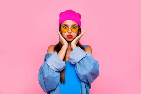 Photo pour Close up portrait of  funny, foolish and young girl puffed her cheeks and hold them with her hands isolated on vivid pink background - image libre de droit