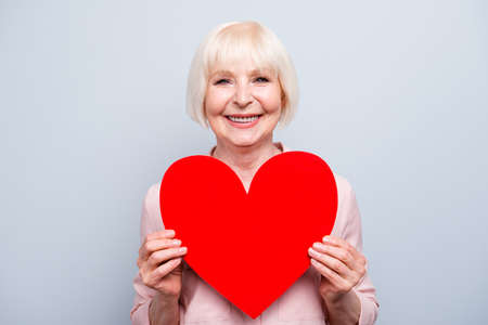 Photo for Portrait of old adult blonde caucasian glad lady holding hands big red paper heart shape, smiling over grey background, isolated - Royalty Free Image