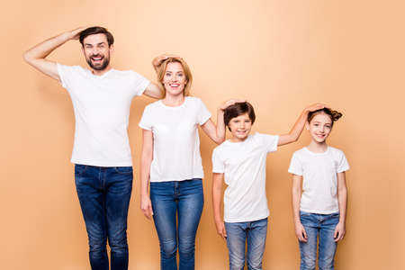 Photo pour Portrait of young beautiful family, bearded father, blonde mother and their little children wearing jeans and white T-shirts, standing in order of hierarchy, placing hands of heads of each other - image libre de droit