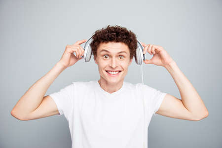 Photo pour Portrait of young handsome and attractive guy dresses white headphones on his head that you listen to good music isolated on light gray background - image libre de droit