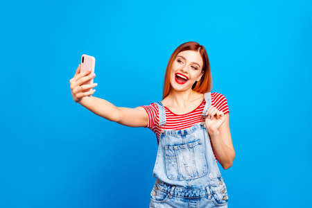 Photo pour Portrait of nice vivid red straight-haired excited happy smiling young girl with opened mouth taking self picture, isolated over blue background - image libre de droit