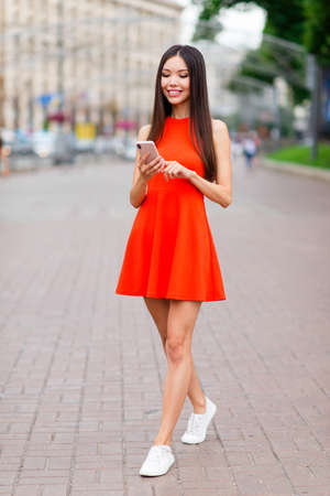 Photo pour Full-size vertical portrait of pretty and calm Asian girl in red mini dress and white sneakers, with phone in hands strolling through the city on a sunny summer day - image libre de droit
