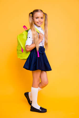 Photo pour Full length, legs, body, size vertical profile side view photo of gorgeous, good-looking small girl in skirt stand half a turn isolated on yellow background hold backpack on shoulder - image libre de droit