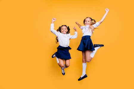 Foto de Dynamic images. Motion, movement, action concept. Full length, legs, body, size portrait of carefree, careless, adorable, beautiful, small girls jumping isolated on yellow background - Imagen libre de derechos