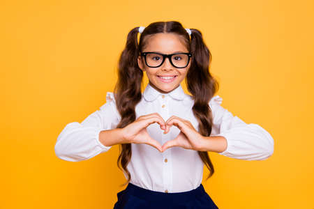 Foto de Portrait of cheerful, joyful, nice, lovely, sweet small brunette girl isolated on yellow background makes heart with her hands - Imagen libre de derechos