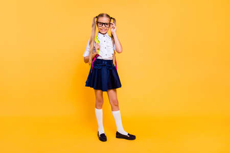 Foto de Full length, legs, body, size portrait of sweet, small blonde girl stand isolated on shine yellow background with copy space for text corrects glasses and looks directly at the camera - Imagen libre de derechos