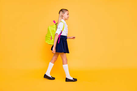 Foto de 1-september concept. Full length, legs, body, size vertical profile side view photo of small girl isolated on yellow background with yellow backpack on shoulders - Imagen libre de derechos