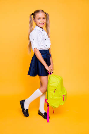 Foto de Full length, legs, body, size vertical profile side view photo of carefree, lovely, sweet, adorable small blonde girl stand isolated on shine yellow background stand half-turn, hold backpack in hands - Imagen libre de derechos