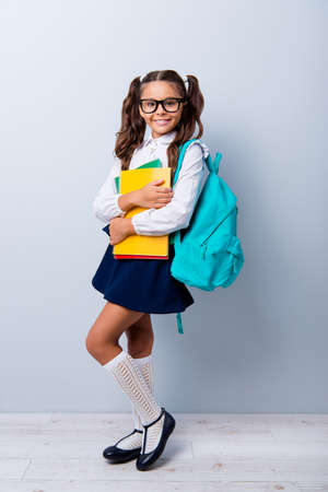 Foto de Full size body length of cute cheerful lovely stylish adorable small little girl with curly pigtails in white blouse shirt and blue skirt, holding color book pile, folders. Isolated on grey background - Imagen libre de derechos