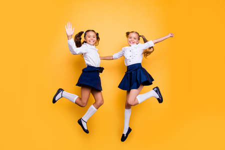Foto de Dynamic images. 1-september concept. Full length, legs, body, size portrait of careless, cheerful, small girls in dark blue skirt, white blouse and black shoes jumping isolated on yellow background - Imagen libre de derechos