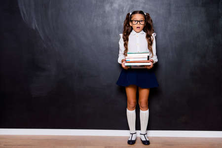 Foto de Full size body length of tired nice smart cute small little girl with curly pigtails in white blouse shirt and blue short skirt, carrying heavy book pile. Isolated over black background - Imagen libre de derechos