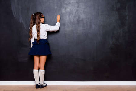 Foto de Back rear view of nice genius adorable small little girl with curly ponytails in white formal blouse shirt, short blue skirt, writing on blackboard. Isolated over black background - Imagen libre de derechos