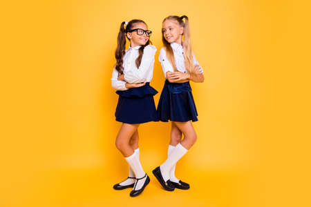 Foto de Full length, legs, body, size portrait of beautiful, pretty, charming, lovely, sweet small girls stand back-to-back with crossed arms took to each other isolated on shine yellow background - Imagen libre de derechos