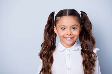 Foto de First grade schoolkid. Portrait of nice cute cheerful positive latin ethnicity girl with curly pigtails in white formal shirt. Copy-space, isolated over grey background - Imagen libre de derechos