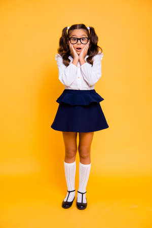 Foto de I'm not ready back to school! Full length, legs, body, size vertical portrait of restless small brunette girl in formal wear stand isolated on vivid yellow background touch her cheeks by hands - Imagen libre de derechos