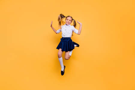 Foto de Full length size studio photo portrait of pretty beautiful cheerful excited nice glad satisfied in white shirt blue skirt schoolkid gesturing hands jumping up isolated bright background - Imagen libre de derechos