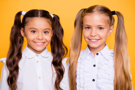 Foto de Close up portrait of beautiful, pretty, charming, gorgeous, adorable, good-looking small girls look directly at the camera isolated on shine yellow background - Imagen libre de derechos