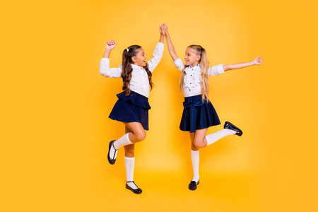 Photo pour Back to school concept. Full length, legs, body, size portrait of beautiful, charming, gorgeous, adorable, good-looking small girls hold hands looking at each other isolated on yellow background - image libre de droit