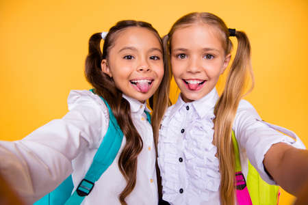 Photo pour Close up portrait of cute, nice, lovely, sweet, adorable small girls take selfie on a smartphone isolated on yellow background look at the camera and show the tongue out - image libre de droit