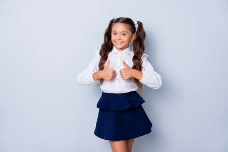 Photo pour Back to school. Nice cute sweet tender cheerful positive small little girl with curly pony-tails in white formal shirt and blue skirt, showing two thumbs-up. Isolated over grey background - image libre de droit