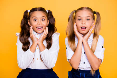 Foto de Close up portrait of cute, nice, lovely, sweet surprised small girls hold hands near the face isolated on yellow background - Imagen libre de derechos