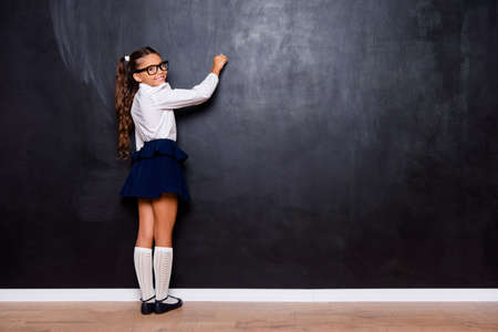 Foto de Full size body length of nice genius adorable lovely small little girl with curly pigtails in white formal blouse shirt, blue skirt, writing on blackboard. Isolated over black background - Imagen libre de derechos
