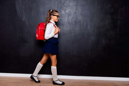 Foto de Full size body length profile side view of nice smart cute stylish small girl with curly pigtails in white blouse shirt and blue skirt with red bag, going to school. Isolated over black background - Imagen libre de derechos
