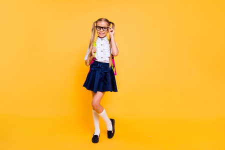 Photo for Full length, legs, body, size portrait of beautiful, charming, gorgeous small blonde girl in skirt stand isolated on shine yellow background with copy space for text corrects glasses - Royalty Free Image