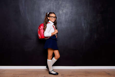 Foto de Full size body length of nice smart cute stylish adorable small little girl with curly pigtails in white blouse shirt and blue skirt with bag. Isolated over black background - Imagen libre de derechos