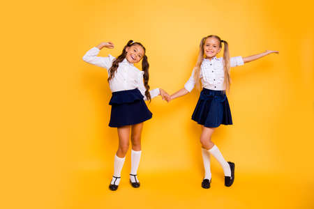Foto de Back to school concept. Full length, legs, body, size portrait of  small girls happily jump holding hands isolated on bright yellow background - Imagen libre de derechos