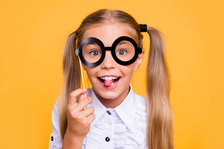 Foto de I do not want to go to school! Close up photo portrait of sweet funky small nice girl holding black big glasses on stick in hand tongue out looking at camera isolated bright color vivid background - Imagen libre de derechos