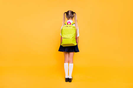 Foto de Full length, legs, body, size back behind rear view photo of girl in blue skirt with yellow lemon rucksack small girl isolated on bright yellow background with copy space for text - Imagen libre de derechos
