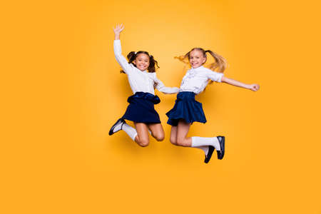Foto de Achievements concept, dynamic images. Full length, legs, body, size portrait of carefree, careless, small girls jumping isolated on yellow background raised fists up - Imagen libre de derechos