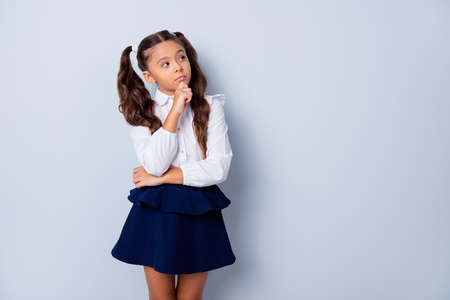 Foto de Nice cute dreamy adorable lovely stylish girl with curly pigtails in white blouse shirt and dark blue shirt skirt, thoughtful gesture, hand fist to chin, copy-space. Isolated over grey background - Imagen libre de derechos