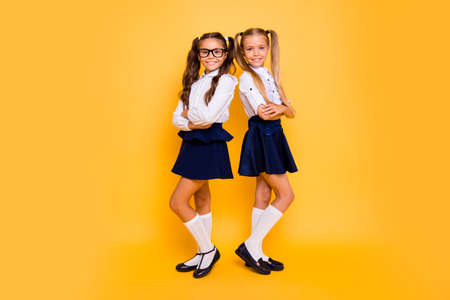 Foto de Full length, legs, body, size portrait of gorgeous, adorable, good-looking small girls stand back-to-back with crossed arms isolated on shine yellow background - Imagen libre de derechos