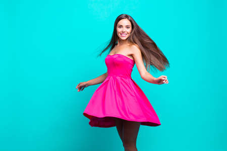 Photo for Young straight-haired sweet brunette smiling girl wearing pink dress, dancing, flirting, wind blows skirt and hair. Copy space. Isolated over bright vivid turquoise background - Royalty Free Image