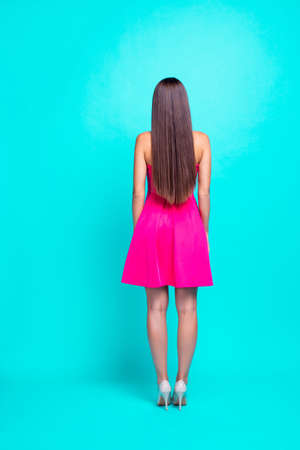 Photo for Rear back full body vertical view of straight-haired sweet tender brunette young girl with long hair, wearing pink mini short dress, standing. Isolated over bright vivid turquoise background - Royalty Free Image