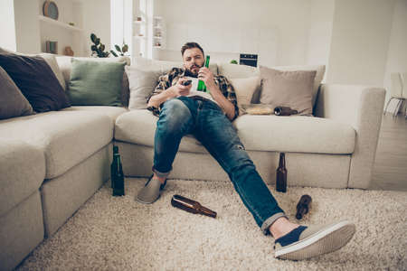 Photo pour Brunet drunk man lies on a white couch at home in blue jeans and - image libre de droit