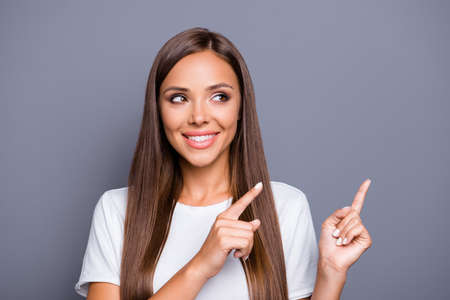 Photo pour Portrait of brown-haired gorgeous attractive nice smiling young lady with logn hair over grey background, showing pointing up and side with fingers, isolated, copy space - image libre de droit