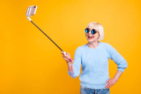 Foto de Young soul grandmother making selfie to the front camera isolate - Imagen libre de derechos