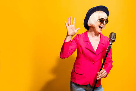 Photo for Portrait of charming modern grandmother holds up the microphone - Royalty Free Image