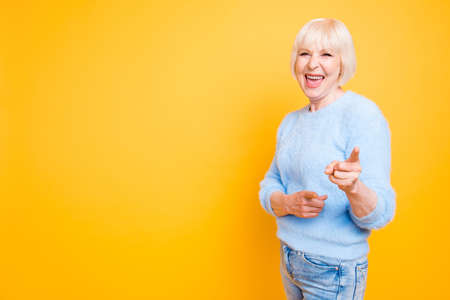 Photo for Portrait of confident modern granny pointing two index fingers a - Royalty Free Image